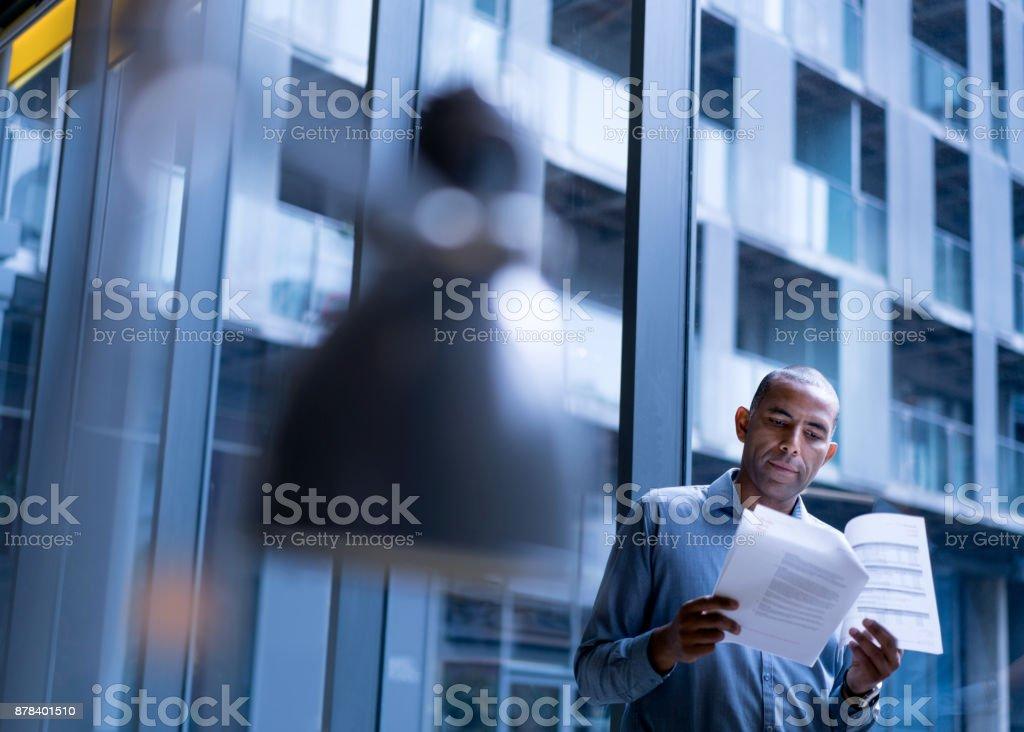 Lesen von Dokumenten durch Bürofenster Geschäftsmann – Foto
