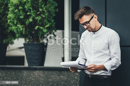 istock businessman reading documents standing on a city street 1138615893