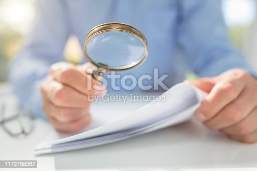 istock Businessman reading documents with magnifying glass 1172735267