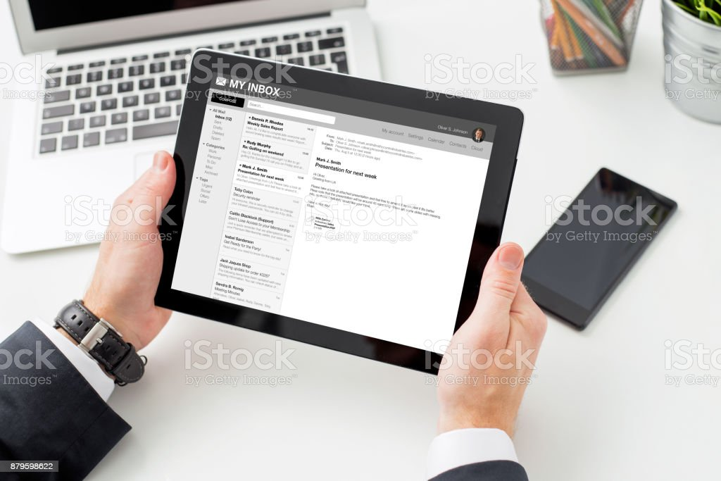 Businessman reading email on tablet computer. stock photo