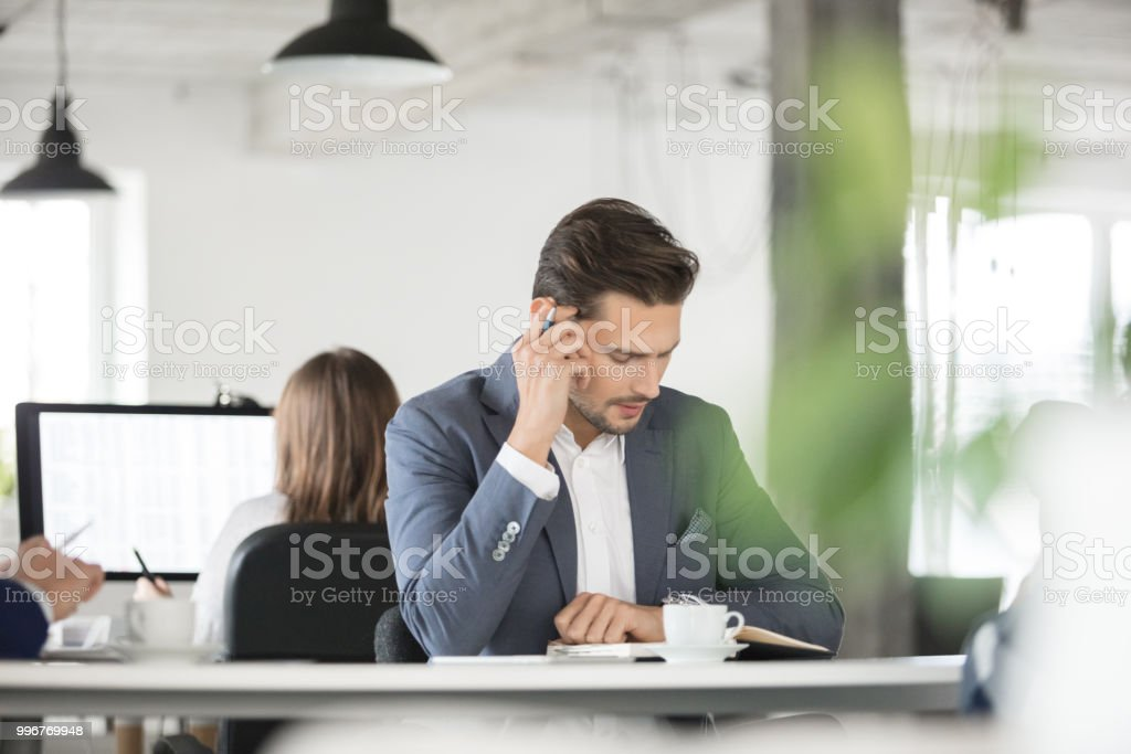 Businessman reading his scheduler Young businessman reading his scheduler while sitting in office. Corporate associate looking at his daily planner dairy. 25-29 Years Stock Photo