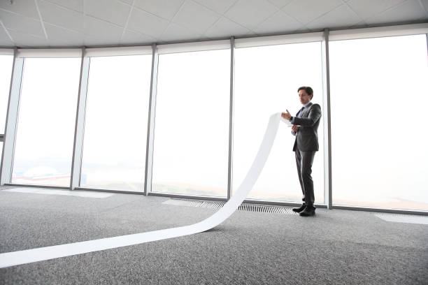 Businessman reading long paper list stock photo