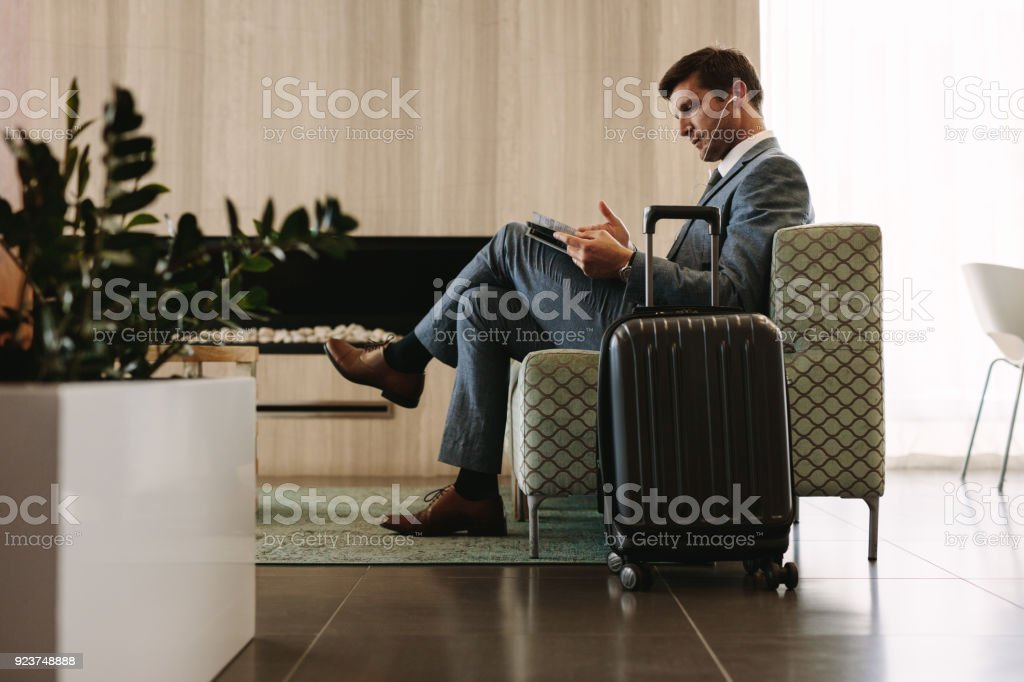 Empresario leyendo revista sala de espera del aeropuerto foto de stock libre de derechos