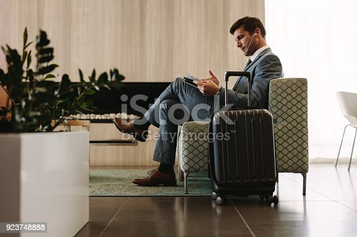 istock Businessman reading magazine in airport waiting room 923748888