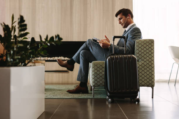 Businessman reading magazine in airport waiting room stock photo