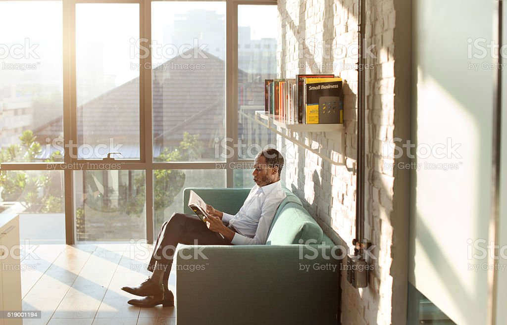 Businessman Reading Magazine Relaxation Concept stock photo