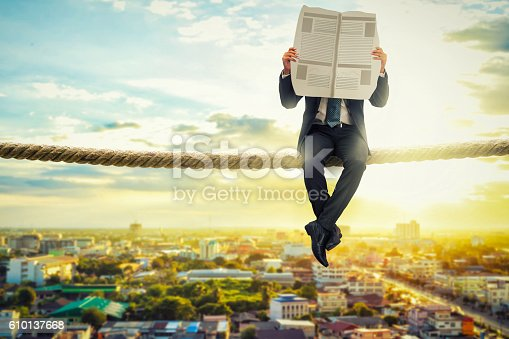 875531516istockphoto businessman reading news paper on rope in the morning 610137668