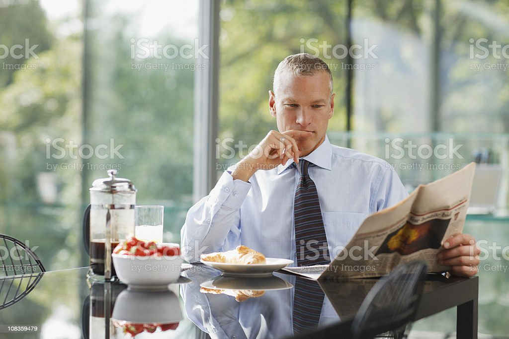 Businessman reading newspaper at breakfast table royalty-free stock photo