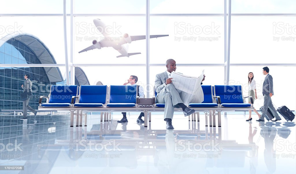 Businessman reading newspaper at international airport gate stock photo