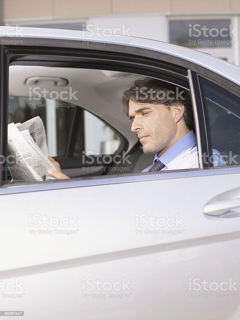 Biznesmen czytanie gazety w tylnym siedzeniu samochodu zbiór zdjęć royalty-free