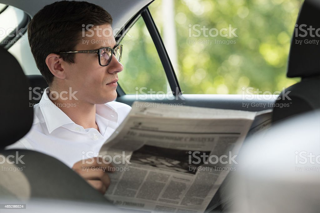 Businessman reading newspaper in his car stock photo