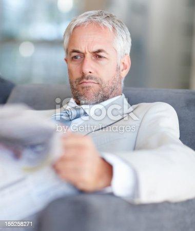 530281733istockphoto Businessman reading newspaper in office 155258271
