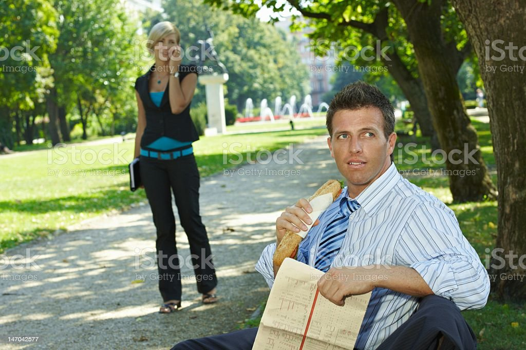 Businessman reading newspaper in park royalty-free stock photo