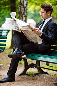 Businessman Reading Newspaper In Park