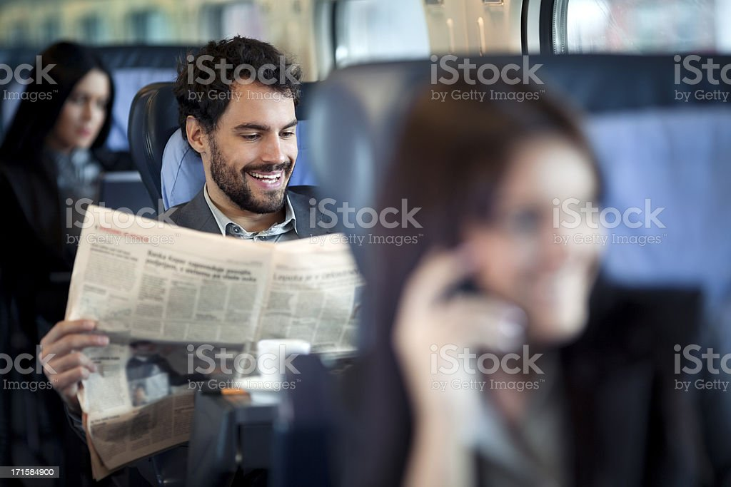 Businessman reading  Newspaper  on a Train stock photo