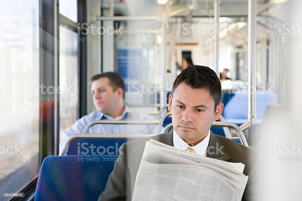 Businessman reading newspaper on train stock photo