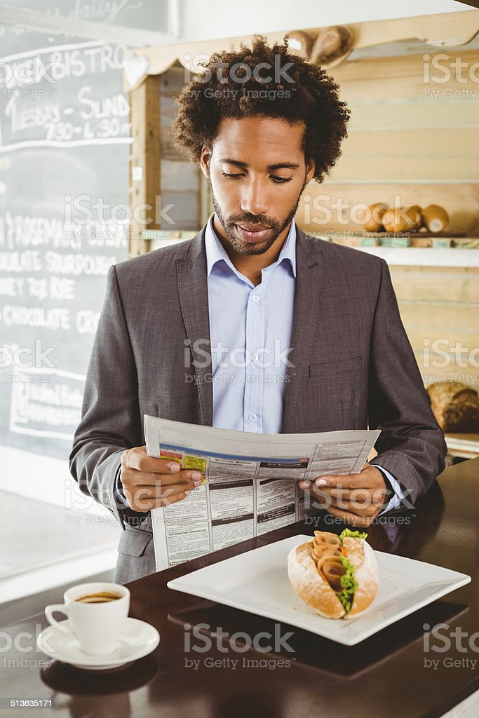 Businessman reading newspaper while having lunch stock photo