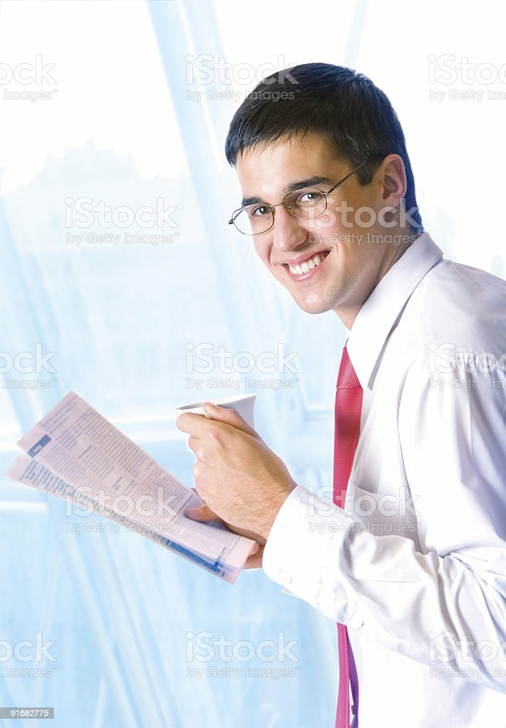 Businessman reading newspaper with tea or coffee at office royalty-free stock photo