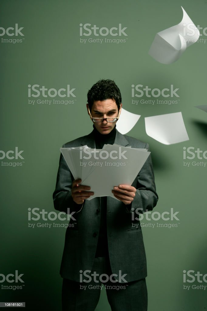 Businessman Reading Papers with Paper Flying Around Him royalty-free stock photo