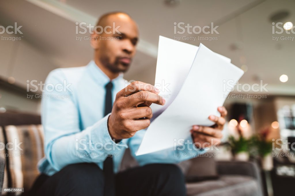 businessman reading rading the bills at home stock photo
