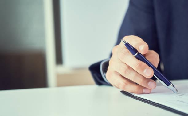 Geschäftsmann liest Mietvertrag vor Abschluss Firmenmann mit Stift in der Hand, der im modernen Büro arbeitet, unterschreibt Geschäftsdokument auf dem Schreibtisch. zusammenrücken. – Foto