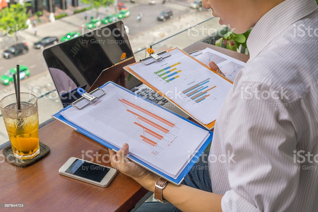 Businessman reading report to understand more about current business situation foto royalty-free