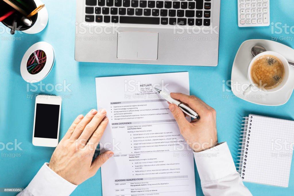 Geschäftsmann Lesung Lebenslauf auf Schreibtisch – Foto