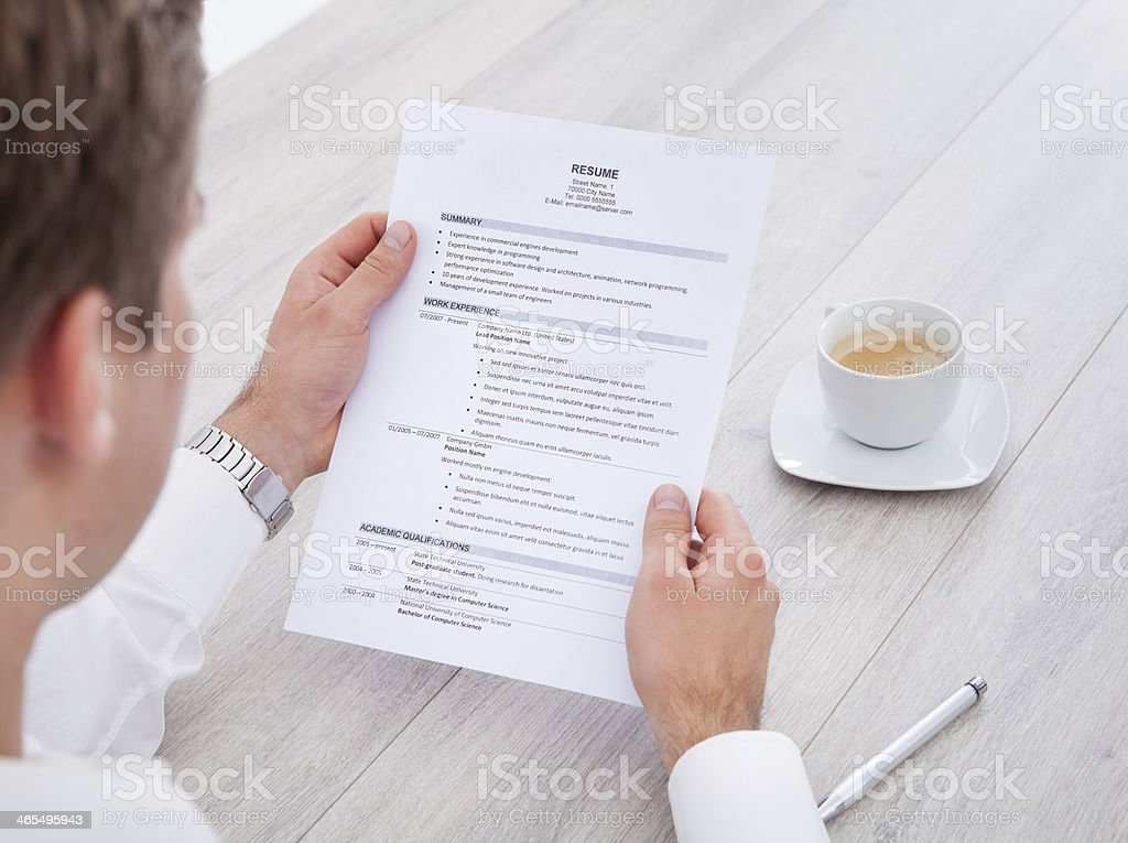 Businessman Reading Resume With Tea Cup On Desk stock photo