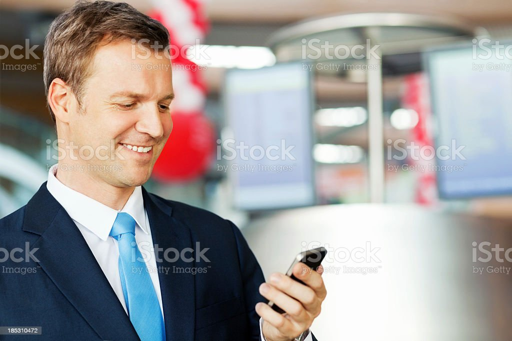 Businessman Reading Text Message At Airport royalty-free stock photo