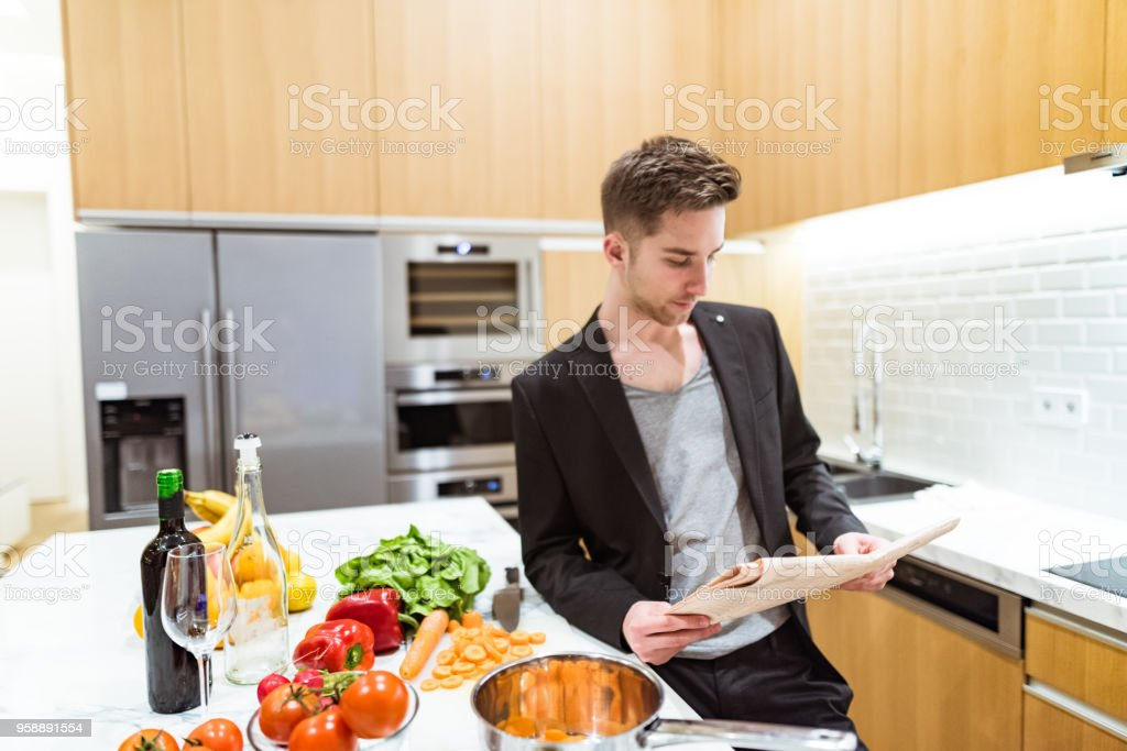 businessman reading the newspaper at home in the kitchen stock photo