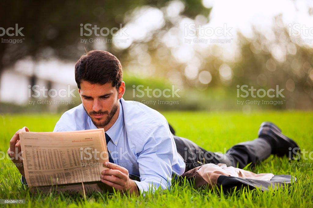 Businessman reading the newspaper stock photo