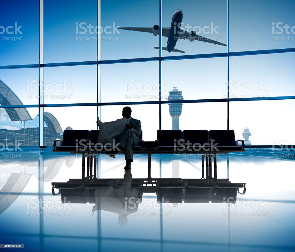 Businessman Reading the Newspaper While Waiting for His Flight stock photo