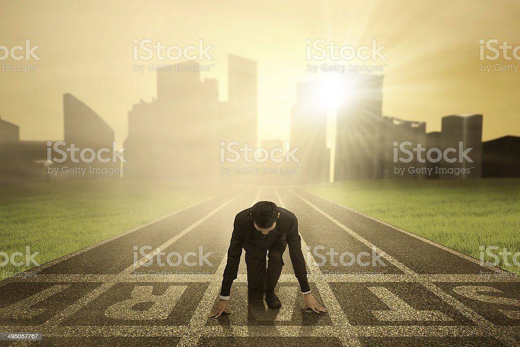 Businessman Ready to Compete Businessman in ready position to race on the track Adult Stock Photo
