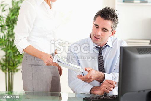 istock Businessman receiving a document from his secretary 855529810