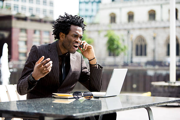 A businessman receiving bad news on his phone stock photo