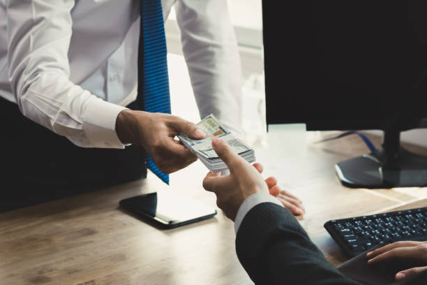 Businessman receiving money from his partner at working desk in the office Businessman receiving money from his partner at working desk in the office - loan, bribery and corruption concepts borrowing stock pictures, royalty-free photos & images