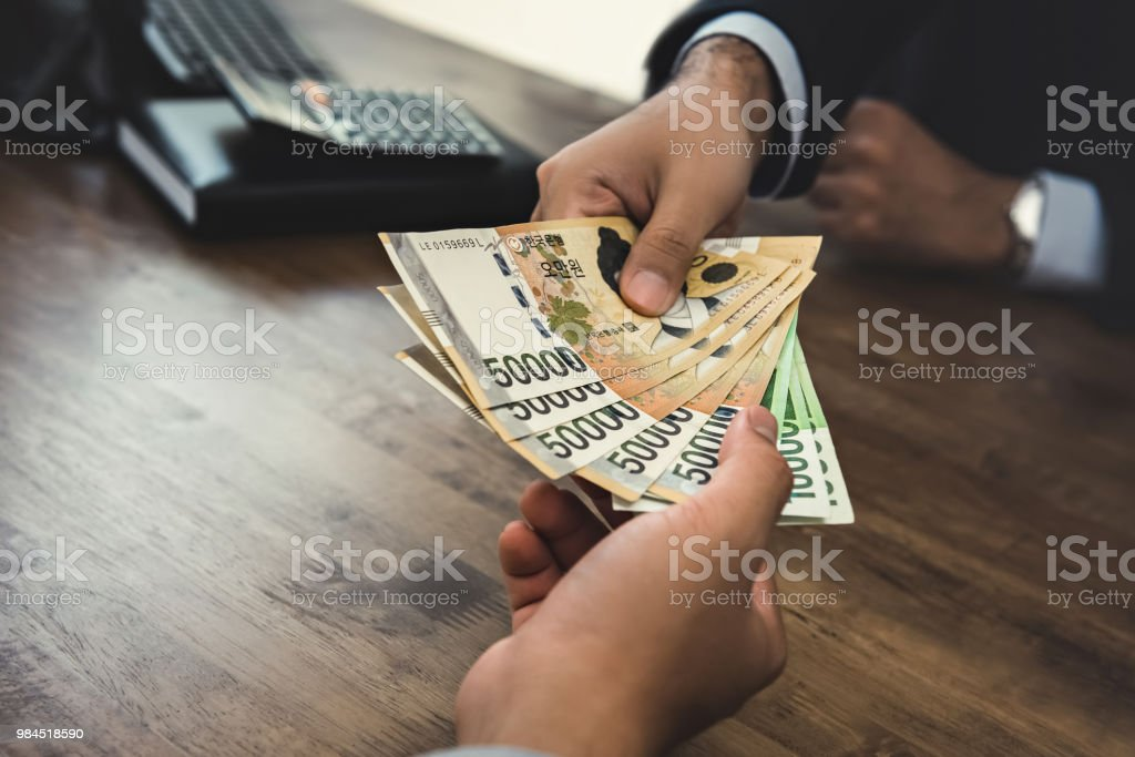 Businessman receiving money, South Korean WON currency bills, hand to hand stock photo