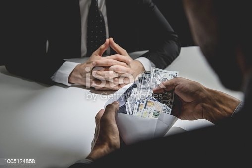 istock Businessman receiving money, US dollars, in the envelope from partner 1005124858