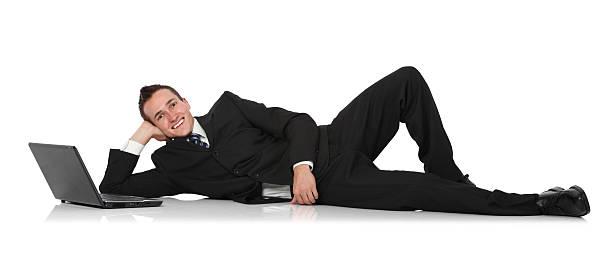 businessman reclining beside laptop - yatmak stok fotoğraflar ve resimler