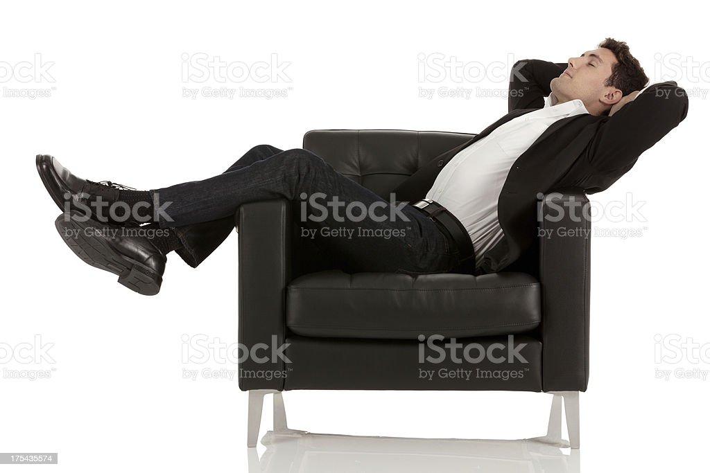 Businessman reclining in an armchair stock photo