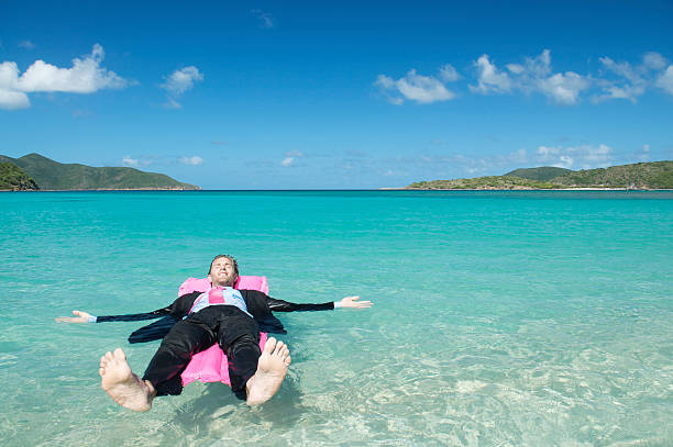 Businessman Reclining on Pink Air Mattress Lilo in Tropical Bay stock photo