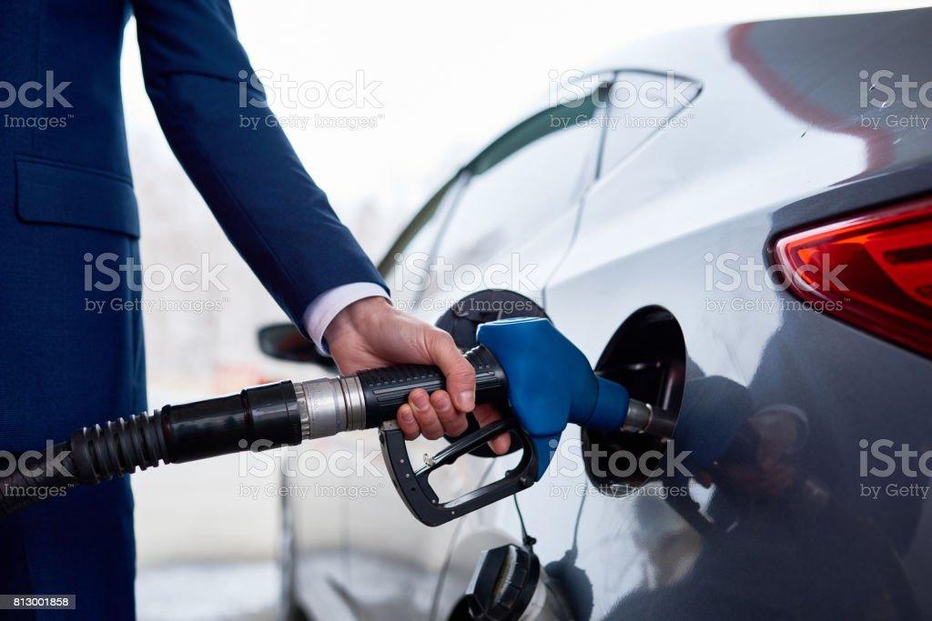 Businessman Refueling Gas Tank in Black Car royalty-free stock photo