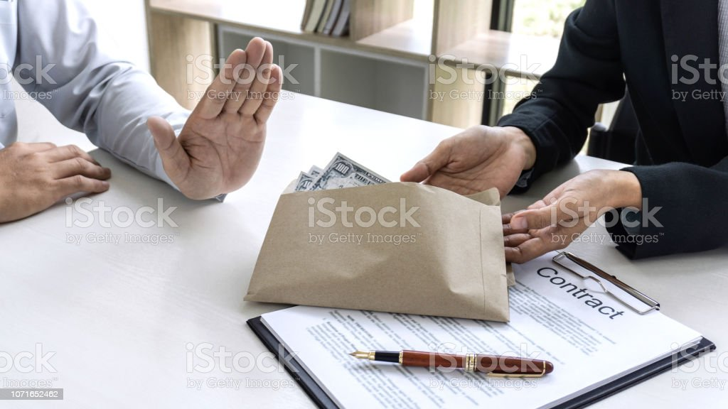 Businessman refuse receive bribe money the form of dollar bills from woman while give success the deal, Bribery and anti-corruption concept stock photo