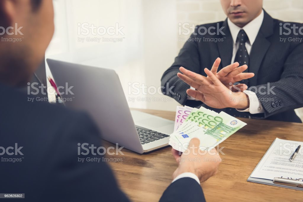 Businessman rejecting money, Euro banknotes, from his partner while making contract agreement stock photo