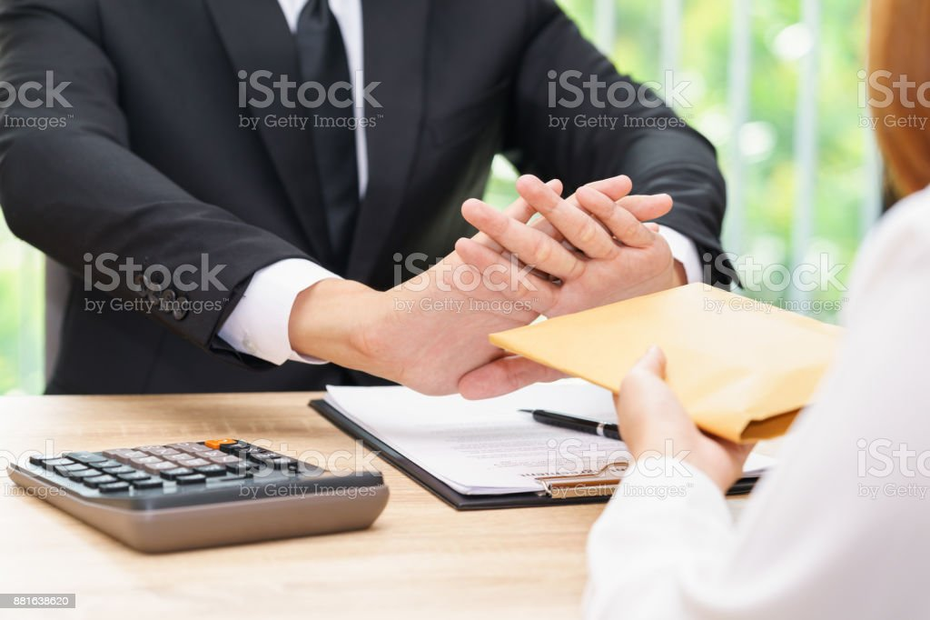 Businessman rejecting money in envelope offered by a woman - corruption concepts. stock photo
