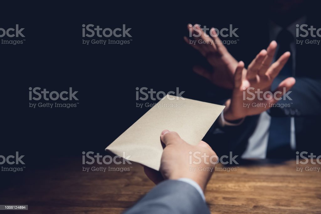 Businessman rejecting money in the envelope, anti bribery concept stock photo