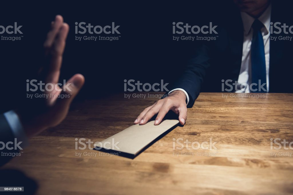 Businessman rejecting money in the envelope stock photo