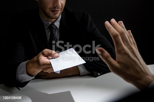 Businessman rejecting money in white envelope offered by his partner in shadow, anti bribery and corruption concept