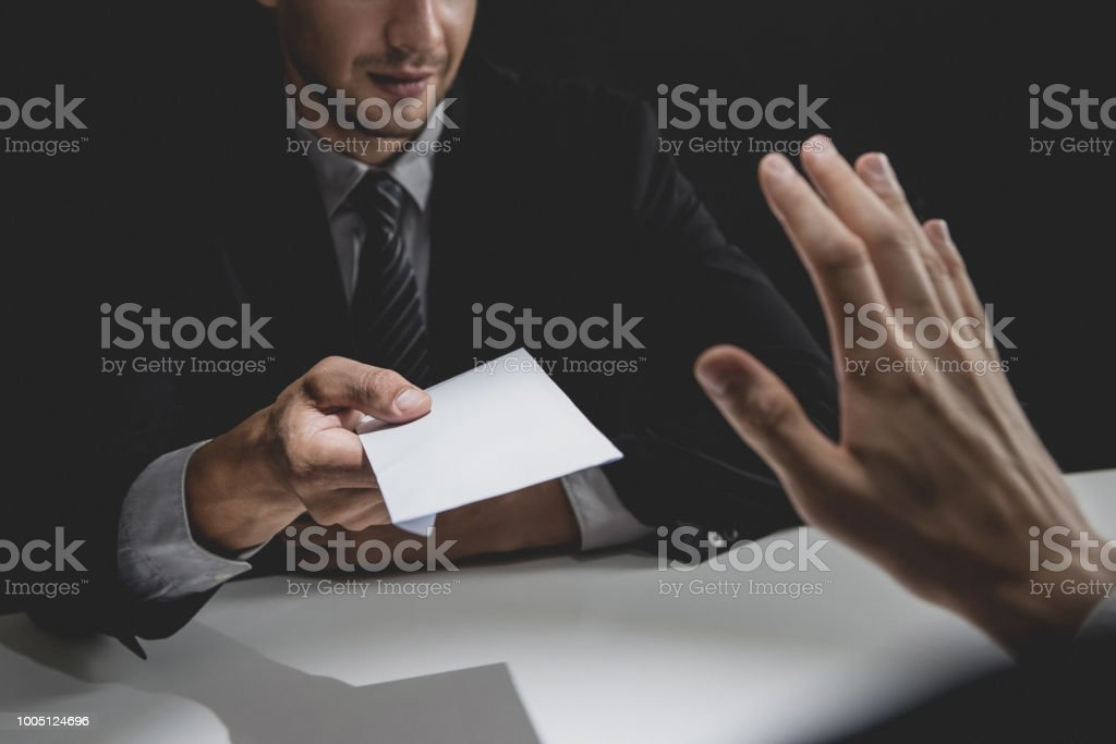 Businessman rejecting money in white envelope offered by his partner in shadow stock photo