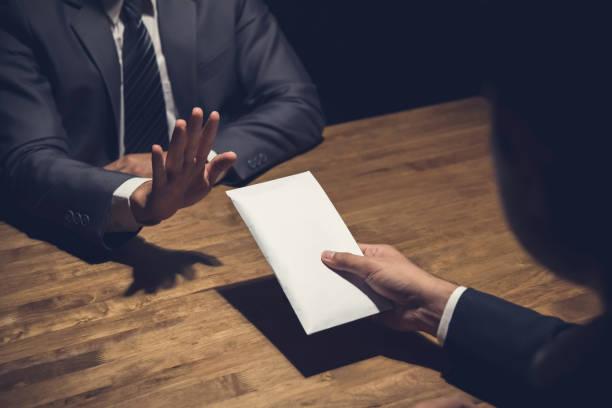 闇の中で彼のパートナーによって提供される白い封筒でお金を拒否するビジネスマン - 腐敗 ストックフォトと画像